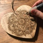 pyrographic mandala tattoo design on wood