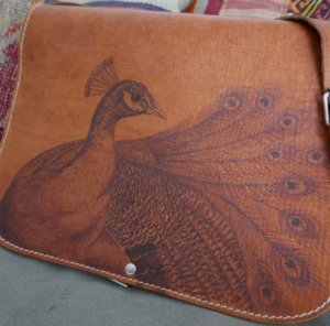 pyrographic artwork on leather bag peacock design