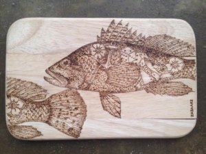 pyrographic artwork on wood cutting board tattooed fish