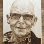 pyrographic portrait on wood of man with glasses